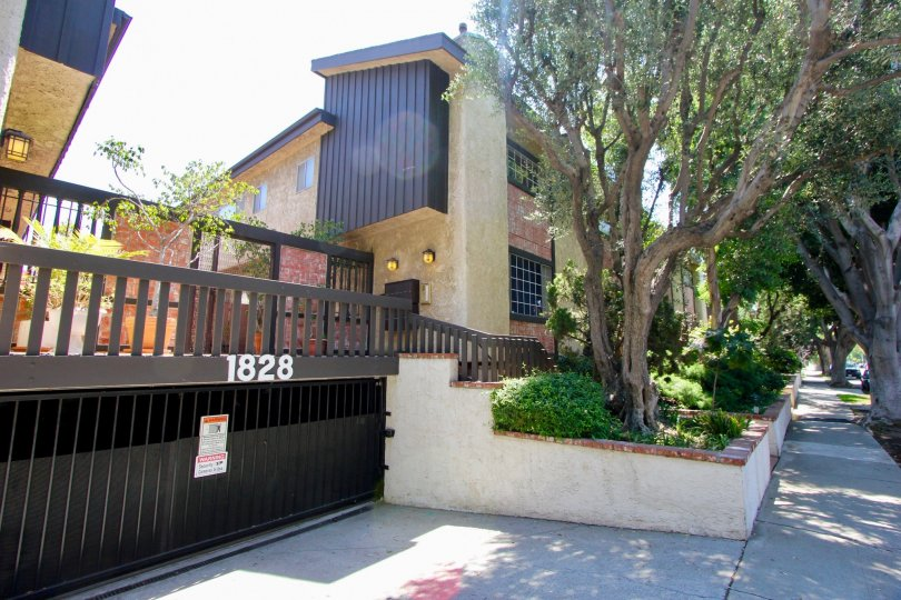 Well dressed trees planted by the right side of the black gate at A cream colored building with black roof at Westside Townhouse in West LA California