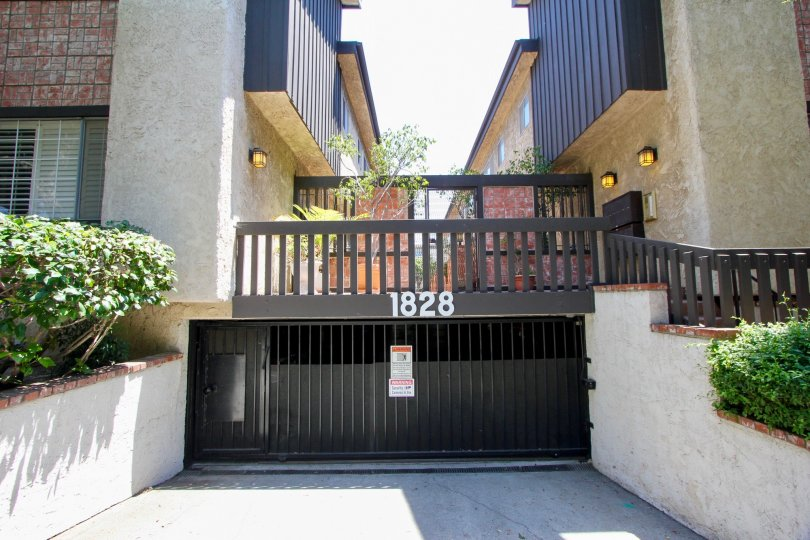 Green plants planted at both sided of the black entrance with number 1828 on it of the Brown brick decorated apartment houses at Westside Townhouse in West LA California