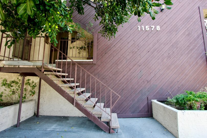 Stairs walk up the side of this wooden condo building and garden planters are near by