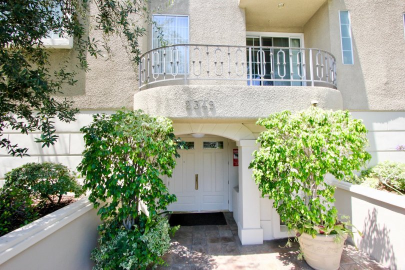 A balcony sits over the entrance to 2349 Beverly Glen. Two potted saplings sit on either side of the entrance.