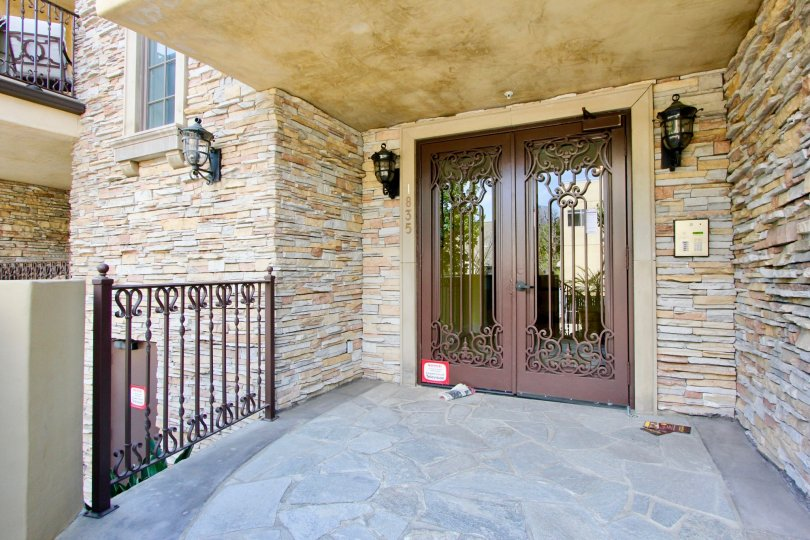 Stone entrance with decorative lamps to Borgata Residence in Westwood, CA.
