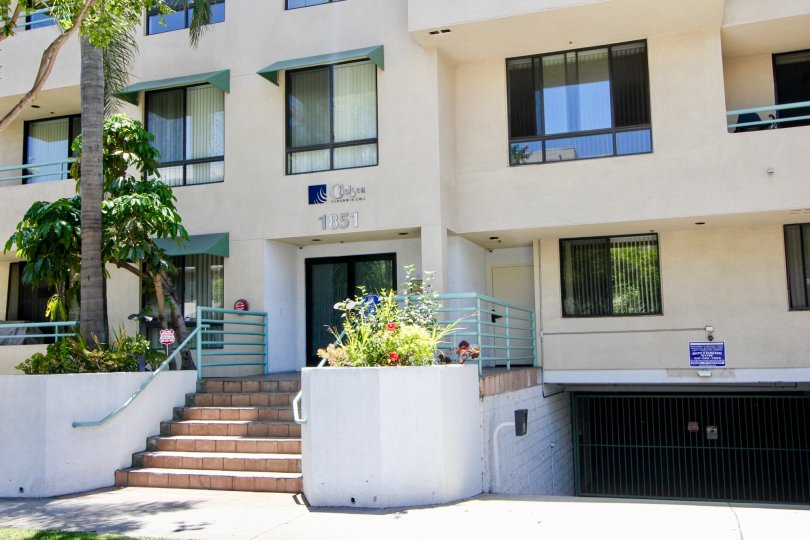 An apartment with car parking area having small garden.