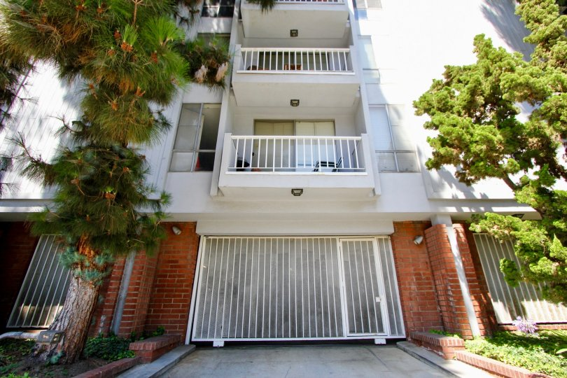 An apartment building in Westwood, CA with two large balconies and a garage under the building