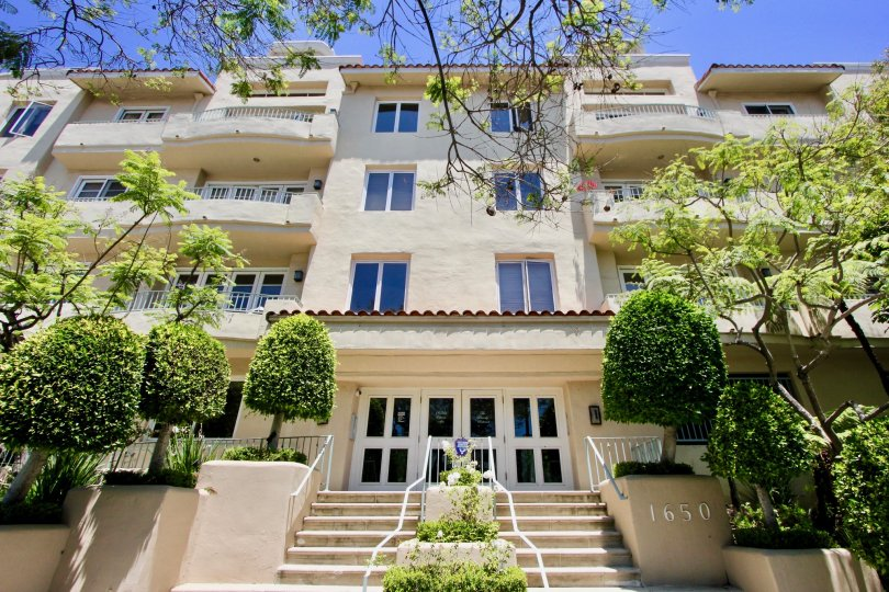 Exterior view of front entrance, stairwell, and balconies of The Beverly Westwood in Westwood, California on a sunny day