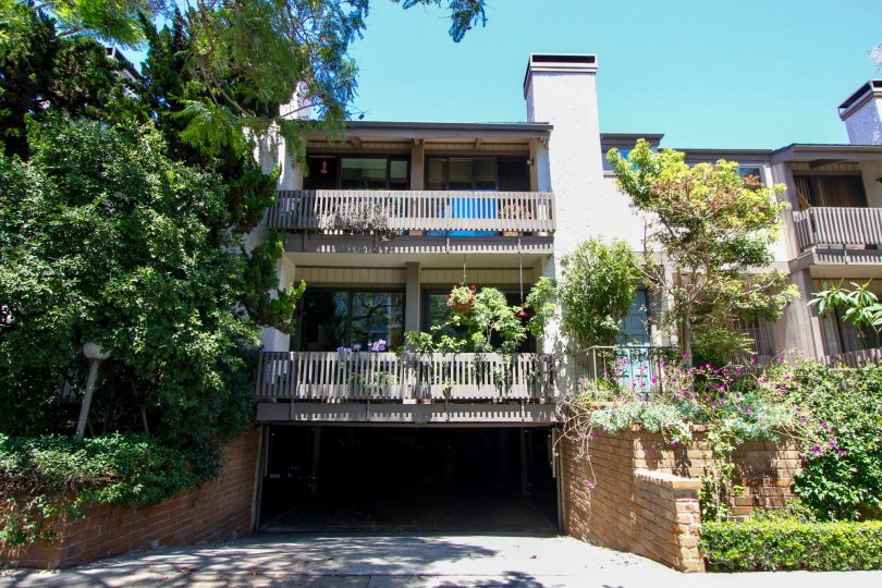 A tan house in the Woodvale Village neighborhood with two balconies and many trees and plants