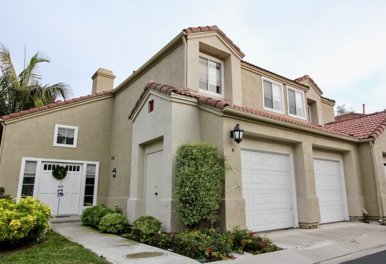 End unit attached home with doulbe car garage with individual doors and stucco siding at California Renaissance