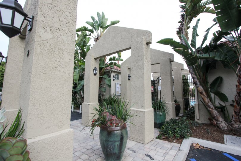 Path to the gate of Apartment in California Renaissance has light lamp and flower pots