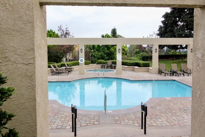 There are some chairs beside the swimming pool in a garden area in California Renaissance