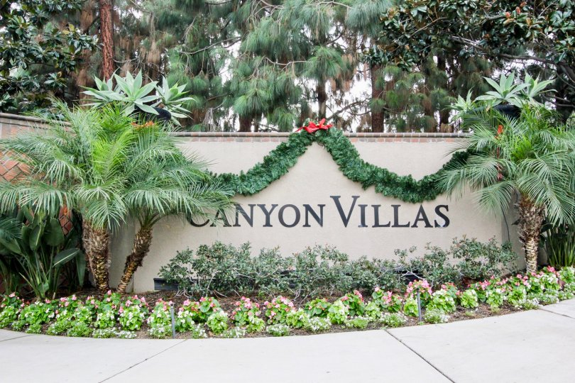 Plants and garland draped over entry sign at Canyon Villas in Aliso Viejo, California