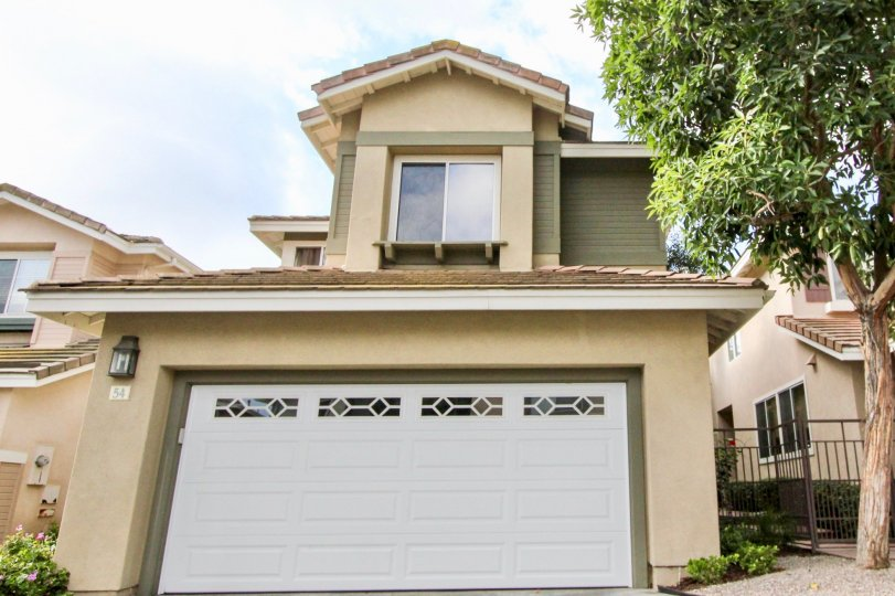 2 storey home with double car attached garage, stucco siding and mature tree with decorative car door at the Cottages