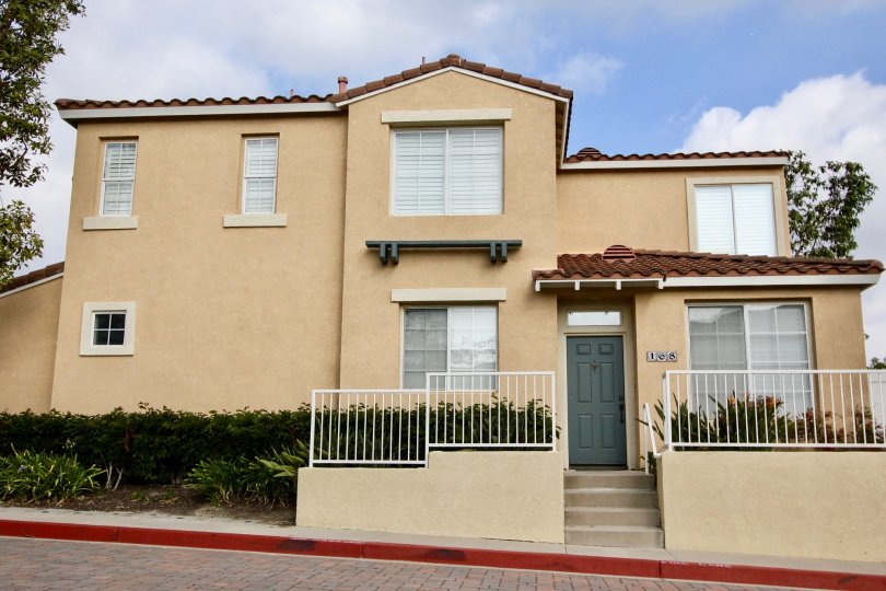 A white fence in front of a two story condominium complex inside the Florest Los Alisos in Aliso viejo CA