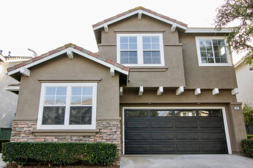 A two story home with a large black garage sits in the community of Harvest in Aliso Viejo, California.