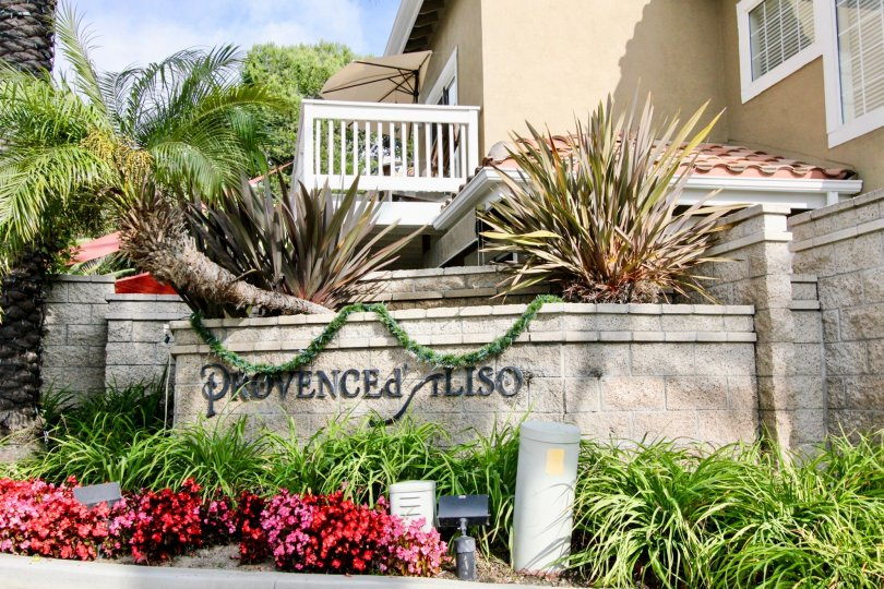 Flowers and landscaping with entrance sign in the Provence D'Aliso community