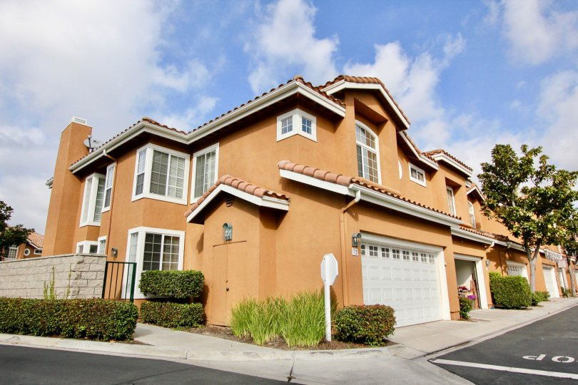 Corner unit home with double car garage, adjacent sidewalk and petite hedges with spanish inspired roof in Aliso Viejo