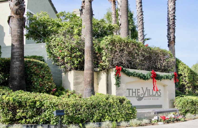 The Villas's sign is surrounded by palm trees and adorned with a festive Christmas garland.