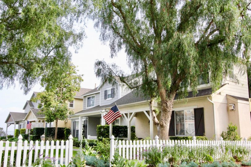 A house in the Twelve Picket Lane community in Aliso Viejo, CA surrounded by a picket fence and large trees