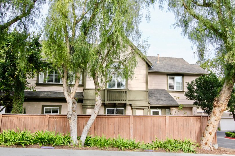 A light wood fence and tall trees surrounds a two story Twelve Picket Lane home.