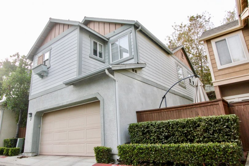 This is a gray house with salmon colored trim and garage with a nice private enclosed patio area