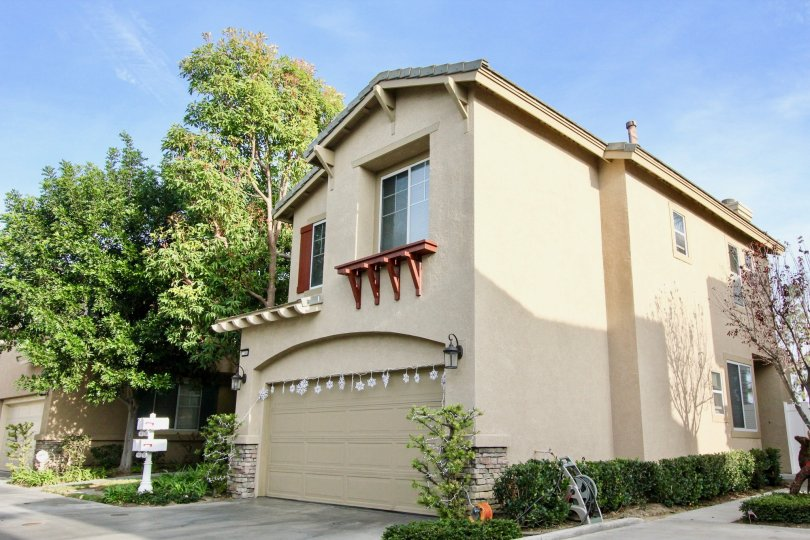 2 storey home with a double car attached garage, 2nd floor planter ledge and mature trees in Aliso Viejo