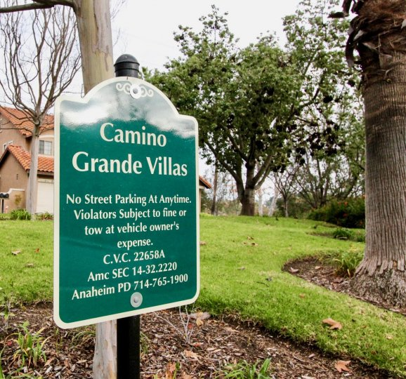 THE HOUSE IN THE CAMINO GRANDE VILLAS WITH THE CAMINO GRANDE VILLAS BOARD, PLANTS, TREES