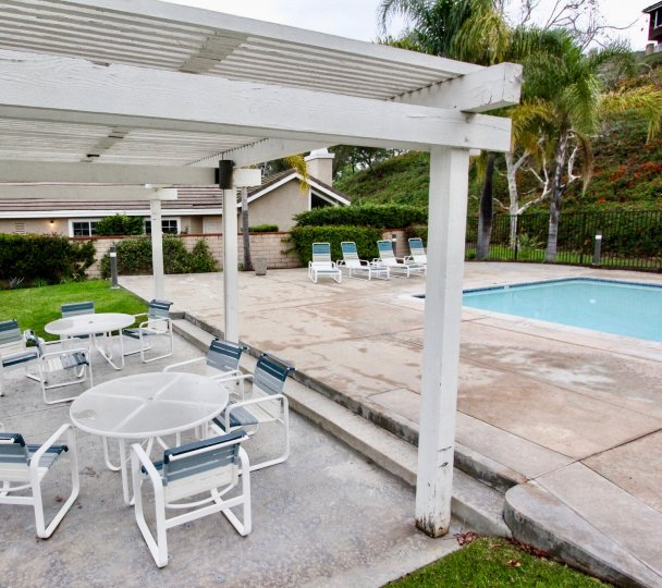 A sunny day in the area of Horizons, pool, beach chairs, palm trees, patio, table, grass, condo