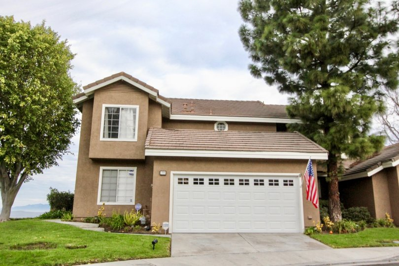 Street view of two-story home with lawn and trees, tan stucco with white trim, in Horizons, Anaheim Hills, CA