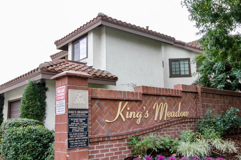 A large pink brick wall with gold writing near homes inside Kings Meadow in Anaheim Hills CA
