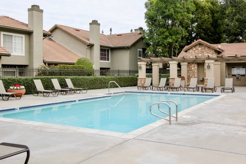 THE FLAT IN THE Laurelwood at Sycamore Canyon WITH THE SWIMMING POOL, CHAIRS, PLANTS, TREES