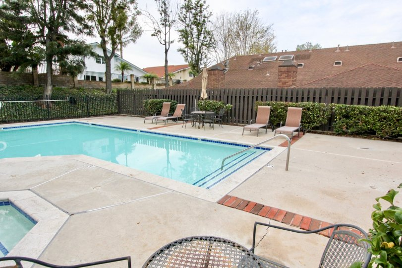 pool with an L shape with house in background and chairs and bushes around