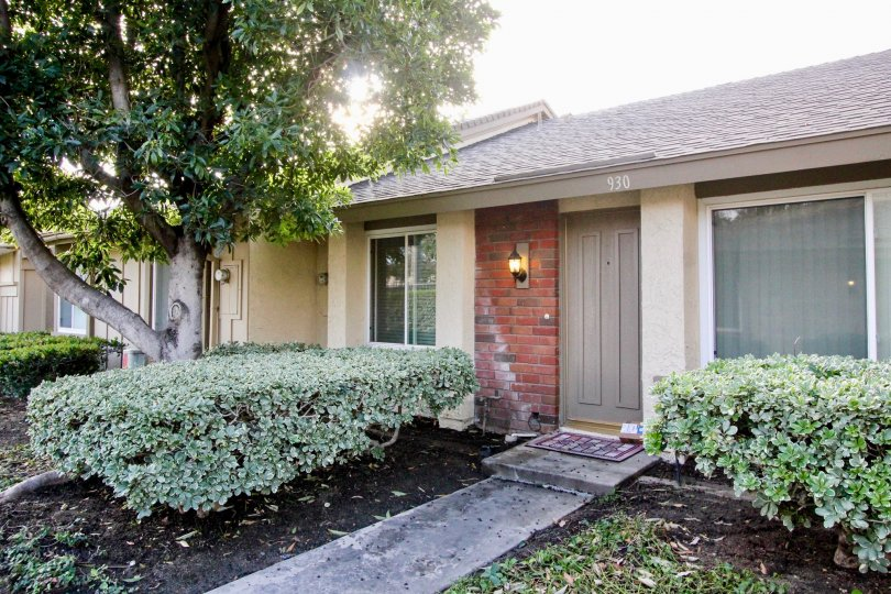 a home with a gray door and brick front and a concrete walkway in Anaheim Gardens