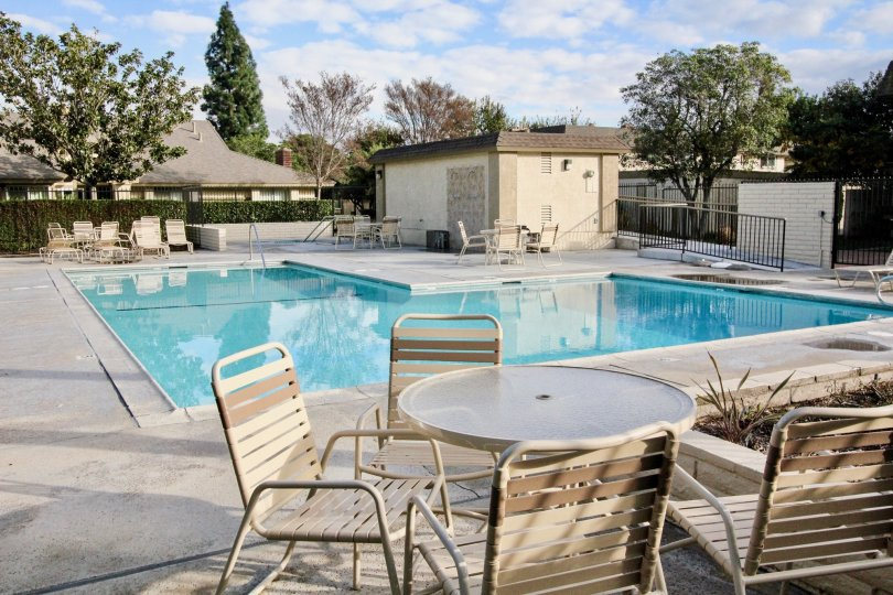 Scene of a pool with tables and chairs at Anaheim Gardens in Anaheim, California