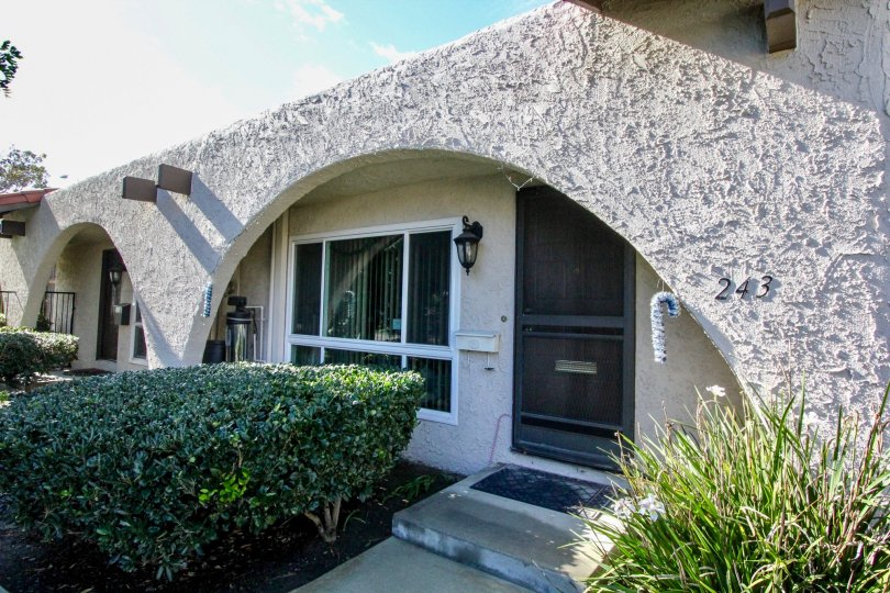 An entry path and front door of a stucco home in Aron Place