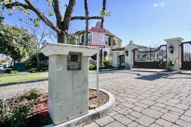 A pillar with a meter in the Cantada Square community with paved driveway and steel gates.