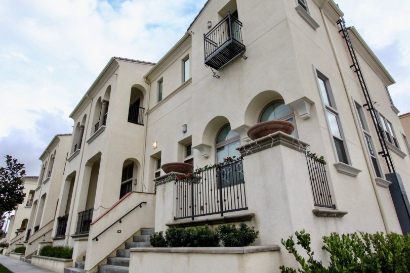 An upward corner view of a townhouse in Circa community with potted pillars and arched windows.