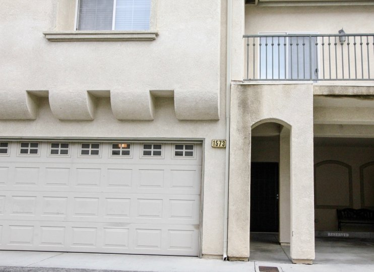 The front of a townhome with a balcony and garage overlooking the street