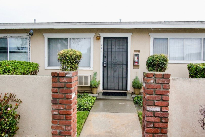 A simple bungalow in the Coco Palms community with gated front door and bricked pillars.