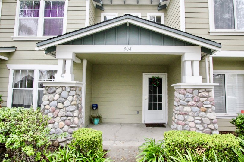 A beautiful porch entry with stone pillars and hedge in Heritage Place Bungalows in Anaheim