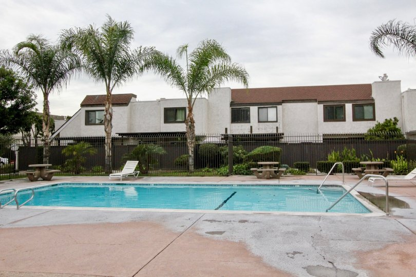 White townhomes with a pool in the Heritage Village Townhomes in the Anaheim, California.