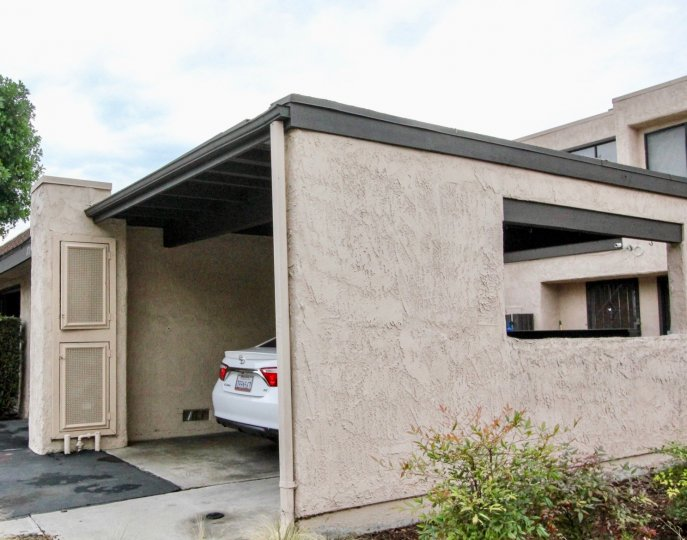 A covered carport, with a white car partially visible, in Heritage Village Townhomes, Anaheim, CA