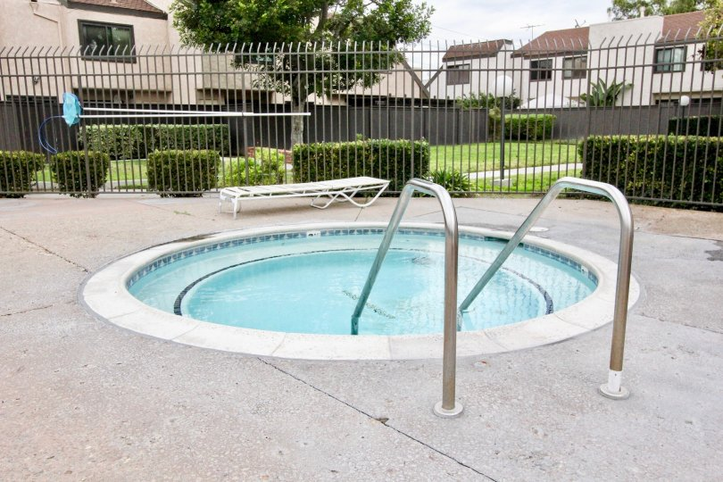 Fabulous round shaped swimming pool with lawn near villas in Heritage Village Townhomes of Anaheim