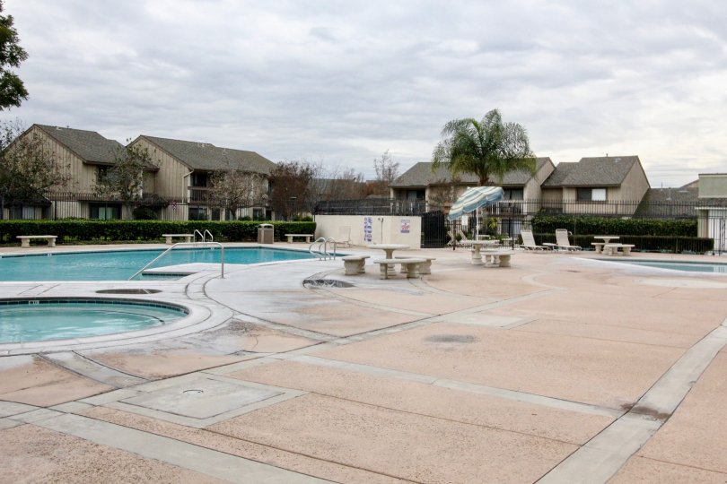 Pool area of the Kaleidoscope apartments in Anaheim, CA. Two pools and a Jacuzzi tub. Several lounge chairs, benches and picnic tables for the communities enjoyment