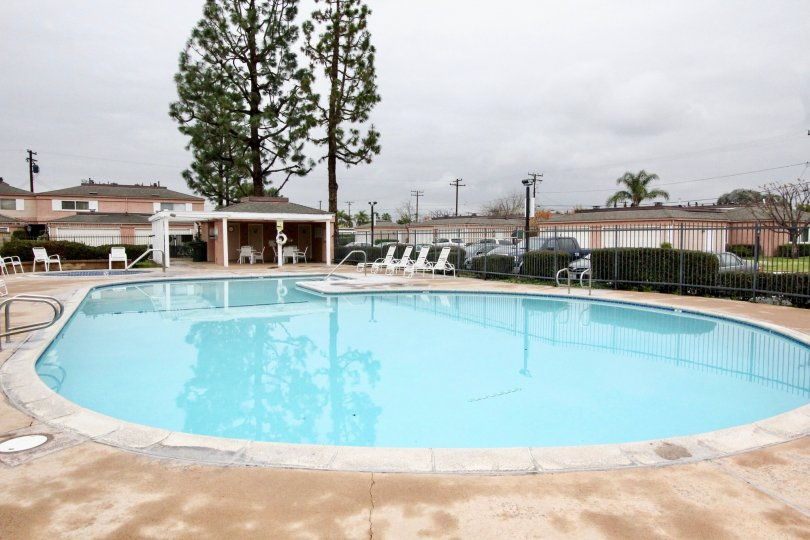 A cloudy day in the Northwoods Village swimming pool with fresh water surrounded by railing and resting chairs in place