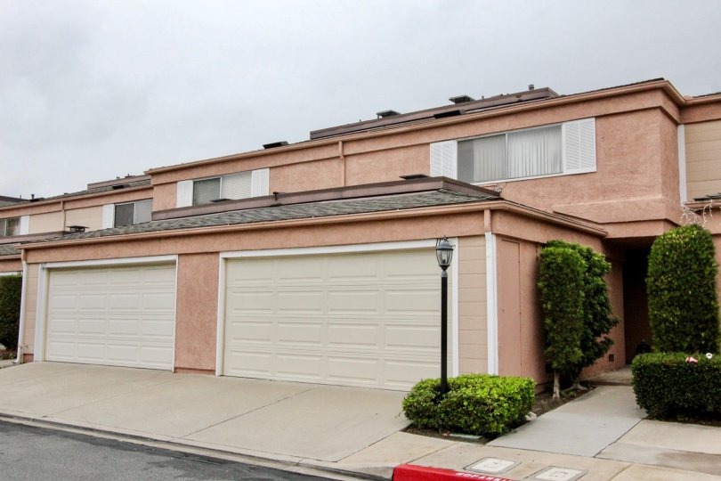 Rose colored condos with two street-facing garages found in the Northwoods Village of Anaheim, California