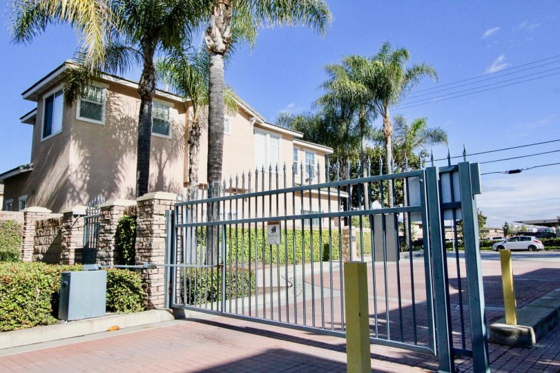 A sunny day in Peppertree Walk with security gate and two story house