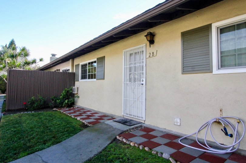 THIS IMAGE SHOWS THE OUTSIDE OF THE HOME THAT HAVE NUMBER ON THE WALL, LAWN, PLANTS ARE THERE IN ANAHEIM CITY