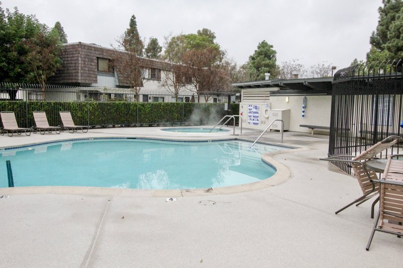 THE SWIMMING POOL WITH LOT OF PLANTS, TREES ARE LOCATED IN ANAHEIM CITY