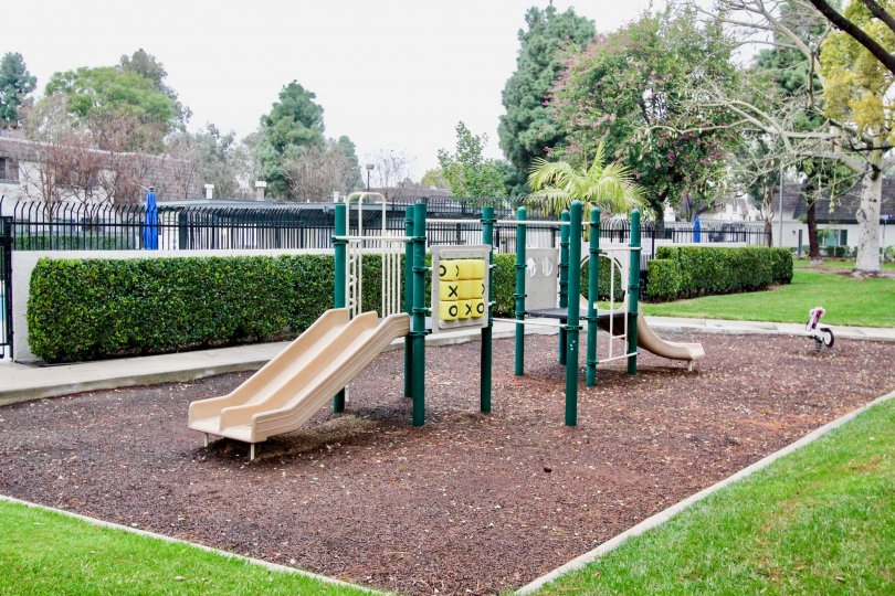 a rainy day in the village green with a park that has children will plays in circus and garden around