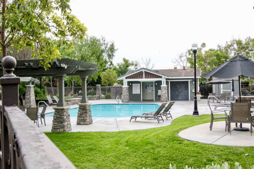 THIS IMAGE SHOWS THE BEAUTIFUL SWIMMINGPOOL IN BUENA PARK THAT HAVE THE LOT OF CHAIRS, LAWN, TREES AND PLANTS