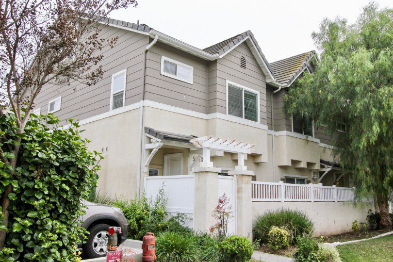 THIS IMAGE SHOWS THE SIDE VIEW OF THE HOUSE WITH PLANTS AND TREES, CAR, LAWN LOCATED IN BUENA PARK CITY