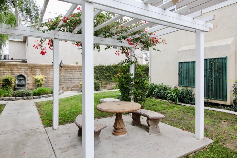 A small shelter in the Trellis Lane with a table and chairs.
